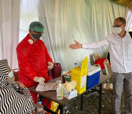 Ketua BPD GBI DKI Jakarta, Pdt. Kiki Tjahjadi, saat berbincang dengan kepala dokter yang melakukan vaksinasi dan berbicang dengan salah satu warga yang divaksin